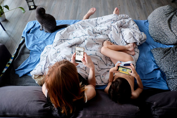 High angle view of people relaxing on bed at home
