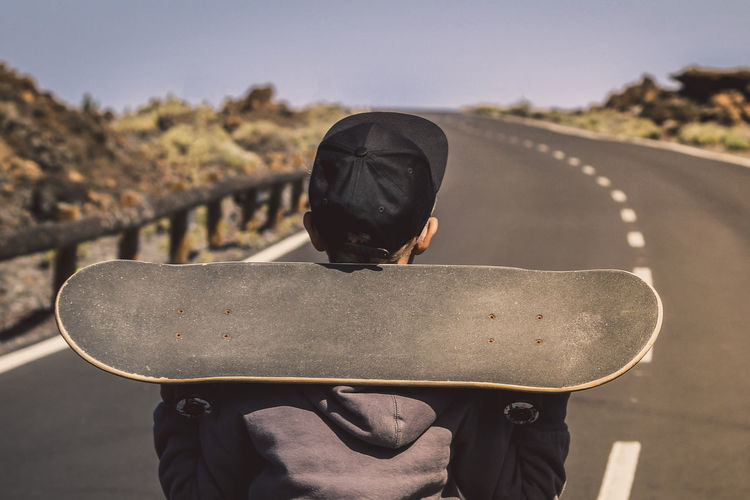 Rear view of boy holding skateboard while standing on road