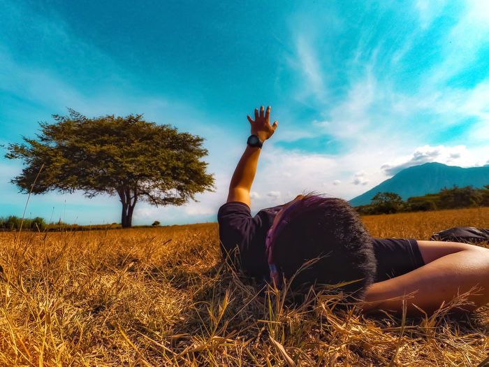 Man gesturing while lying on grassy field against blue sky