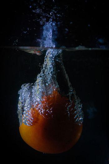 Close-up of orange fruit against black background