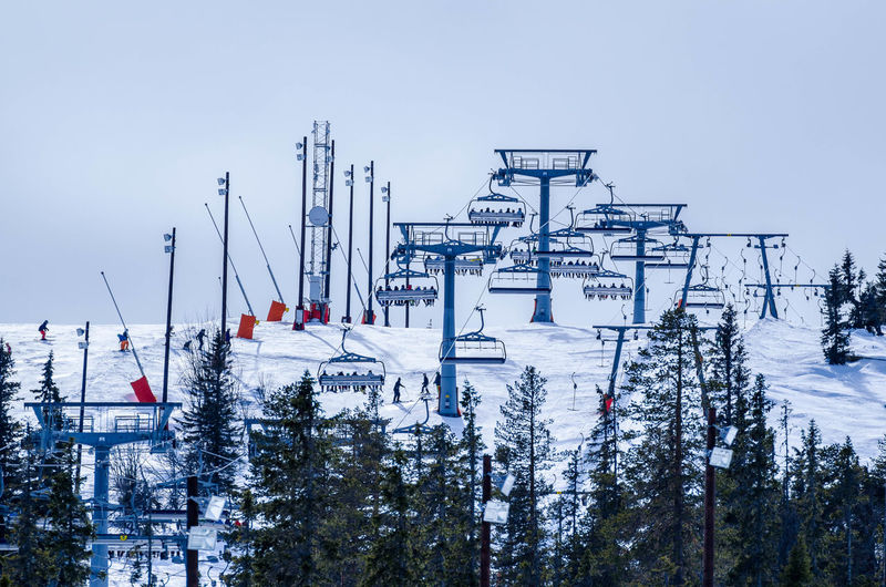 Ski Lifts On Snow Covered Mountain Against Sky