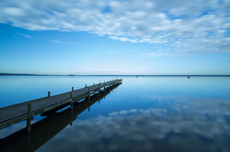 Wooden jetty on calm lake against blue sky and clouds