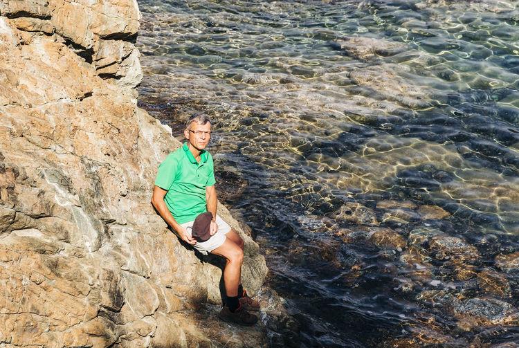 High angle portrait of man sitting on rock