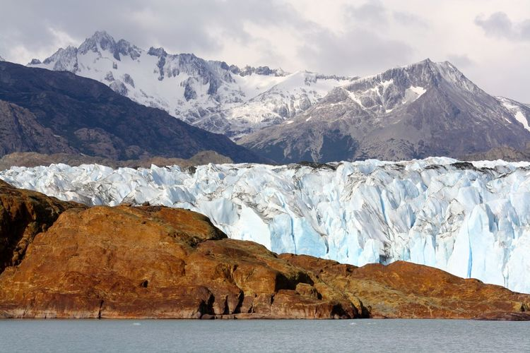 Spectacular mountain range with glaciers and rock at the edge of the sea