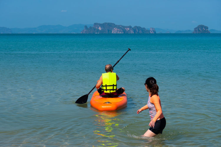 Asian senior father playing standing up paddle board with daughter at blue sea on summer vacation