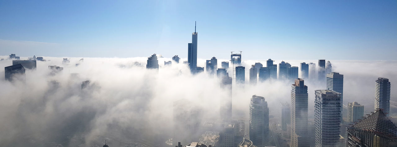 Panoramic view of dubai marina buildings  covered in fog against sky