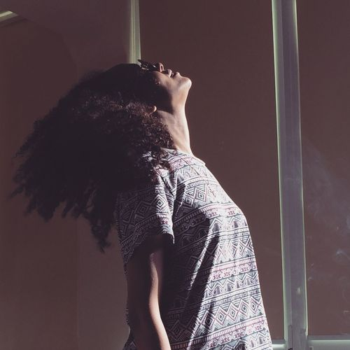 Side view of woman tossing hair while standing against window