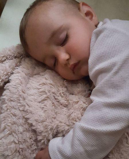 Close-up of baby sleeping on rug