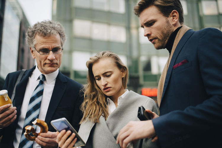 Man and woman using phone while standing in office