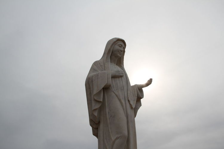 Low Angle View Of Virgin Mary Statue Against Sky
