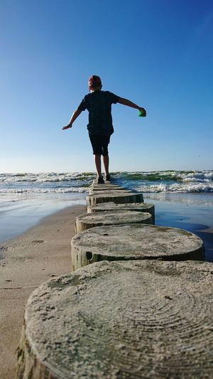 Rear View Of Boy Balancing On Tree Stumps At Beach Against Blue Sky