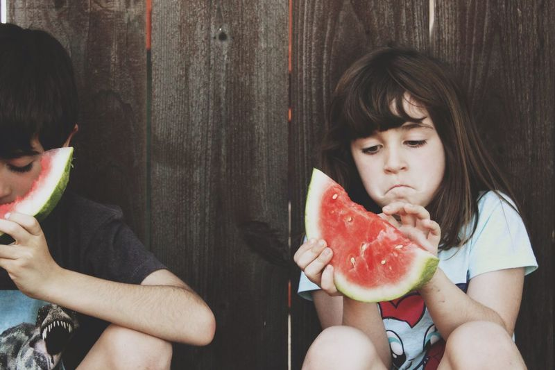 Siblings eating watermelon against wooden fence