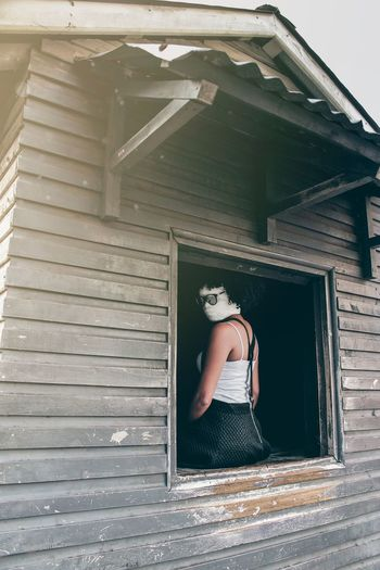 Woman with face covered by bandage sitting on window in house