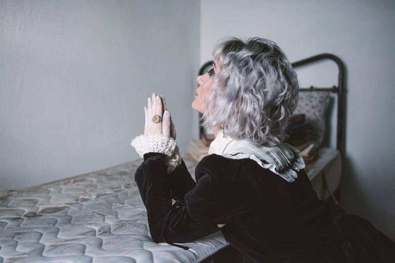 Side view of woman sitting against wall at home