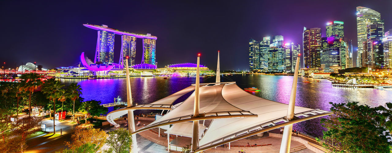 Vibrant color panorama background of Singapore skyline view of skyscrapers on Marina Bay Night Architecture Building Exterior Built Structure Illuminated Water City Building Nature Sky Skyscraper Office Building Exterior Transportation No People Travel Destinations River Landscape Modern Outdoors Cityscape Singapore Marina Bay Sands Panorama Panoramic