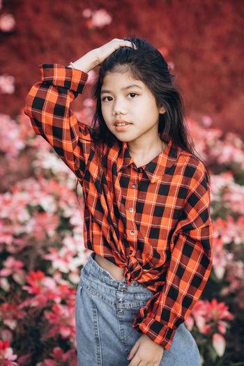 Portrait of cute girl standing against flowering plants outdoors