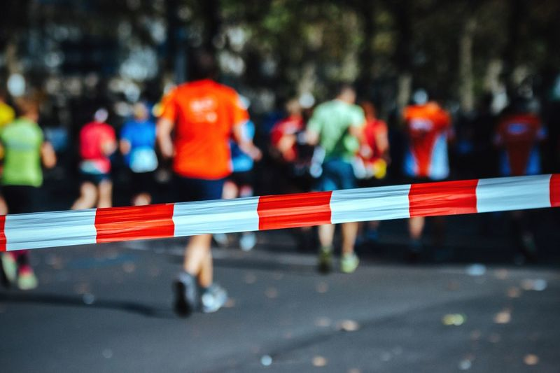 Cordon Tape On Road With People Running In Background During Marathon