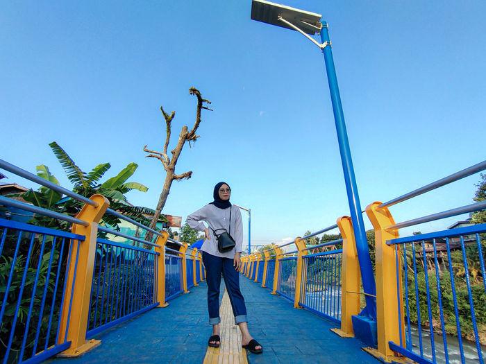 Man standing on railing against blue sky
