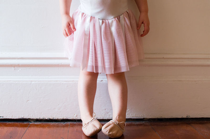 Low Section Of Girl Wearing Ballet Shoes Against White Wall