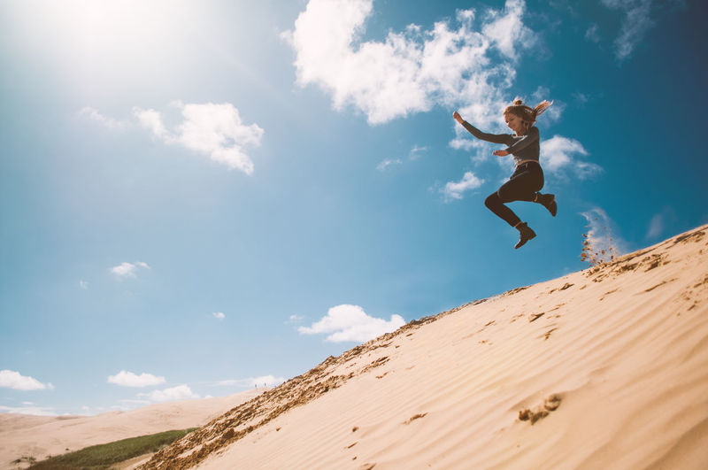 Low angle view of woman jumping in sky