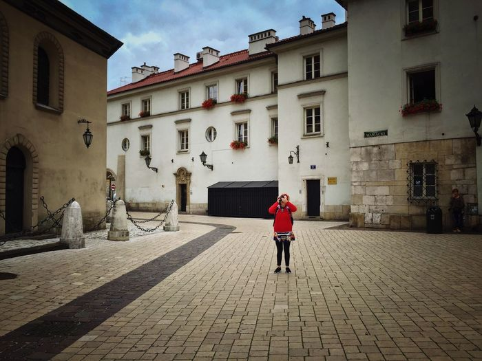 Krakow Streetphotography Red Building Woman Photographer Moments Life Capture The Moment Captured Moment Colorful City Life Composition Vivid People Waiting Square Colors