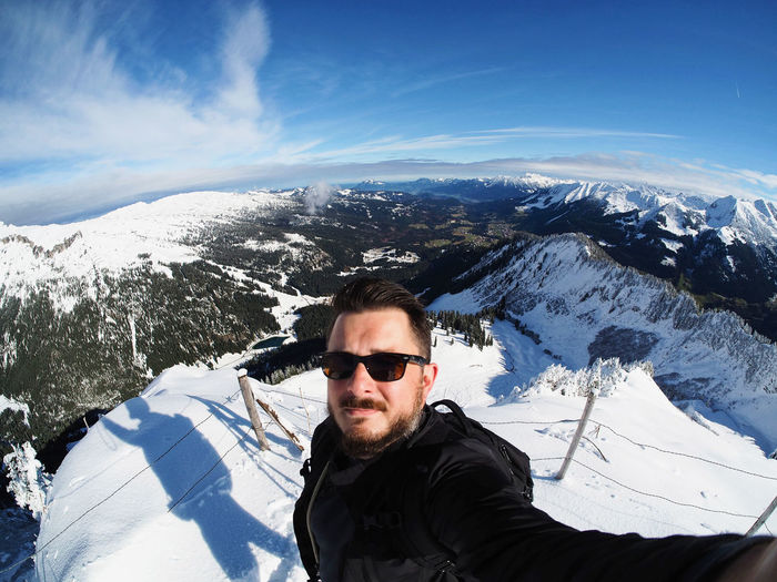 High Angle Portrait Of Man Wearing Sunglasses Standing On Snowcapped Mountain