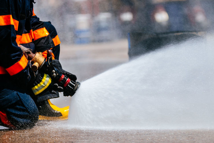 Low section of firefighter spraying water
