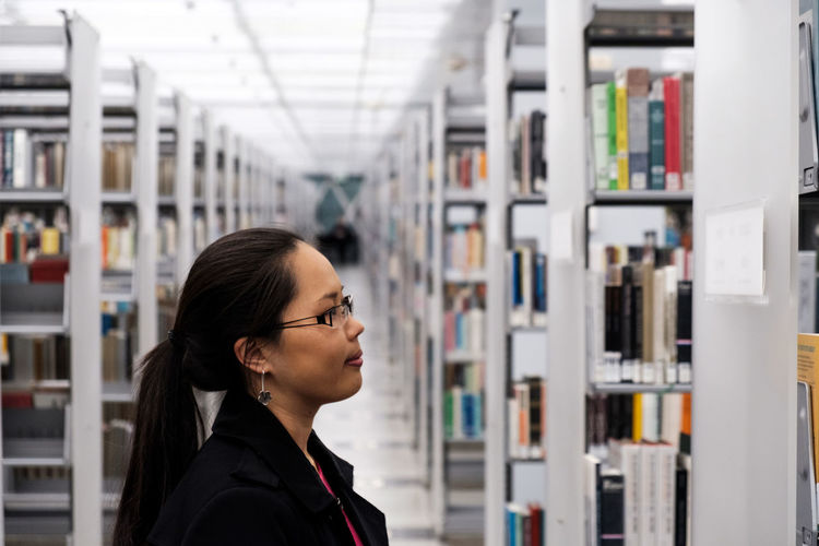 What to read One Person Indoors  Shelf Real People Women Book Glasses Education Portrait Eyeglasses  Headshot Bookshelf Publication Looking Adult Focus On Foreground Learning Young Adult Library Hairstyle Profile View Books Bookshelf Looking Away Searching