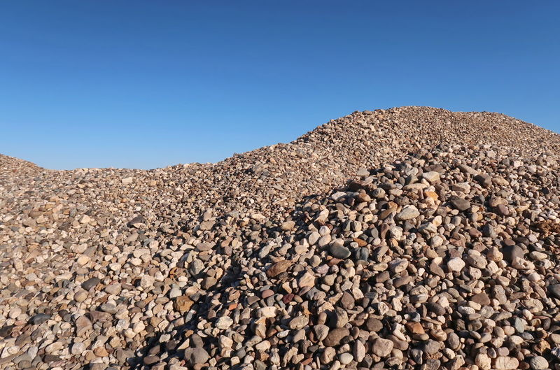 Stack of pebbles on sand against clear sky