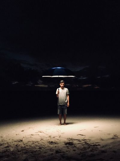 Full length portrait of man holding illuminated umbrella while standing at beach