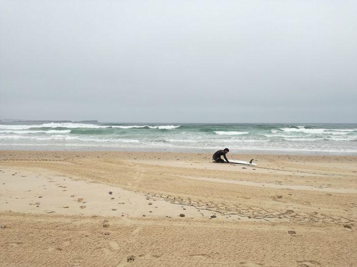 Surfer at beach against sky