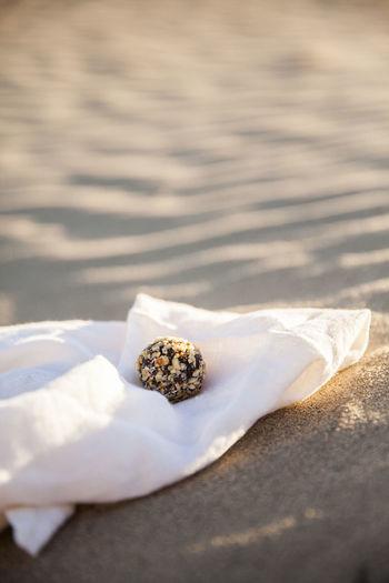 Raw hazelnut energy ball placed on a napkin on a beach