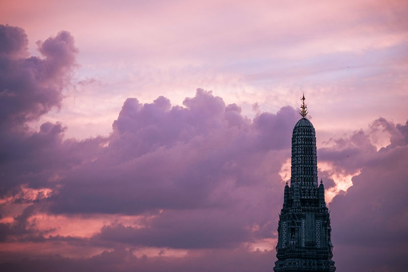 Wat Arun Dome top is seen from across the river at dusk with a cloudy sky in the background. Purple sky creating a stunning view for travelers. Arun Wat Arun Architecture Building Building Exterior Built Structure City Cloud - Sky Financial District  Landmark Low Angle View Nature No People Office Building Exterior Outdoors Sky Skyscraper Spire  Sunset Tall - High The Past Tourism Tower Travel Travel Destinations