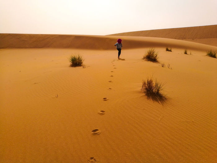 Rear View Of Woman Walking On Desert Against Clear Sky