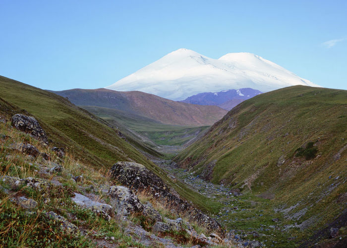 Snow peaks of the Elbrus, Russia Beauty In Nature Grass Inspirational View Panoramic View Peaks Hiking Trail Caucasus Mountains Nobody Nature Photography Environment No People Traveling Meditating Nature Snow Snow Peaks Blue Sky Sunny Day