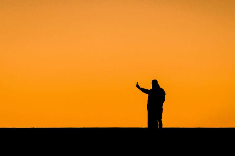 Silhouette People Standing Against Clear Orange Sky