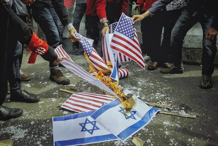 Indonesian muslim burn Israeli and U.S. flags during a protest in front of U.S Embassy in Jakarta, Indonesia, on December 15, 2017 against the U.S. President Donald Trump's decision to recognize Jerusalem as Israel's capital. Save Palestine Palestine Free For Palestine Yerusalem Is Palestine Usflag Israel Flag American Flag Burn Flag Us Embassy Jakarta Protester Demonstrants Fire Flag People Power Editorial  Patriotism Flag Striped Men Politics People Outdoors Military