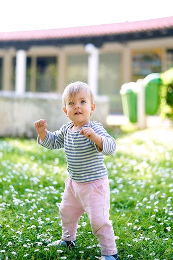 Full length of cute baby girl standing on field