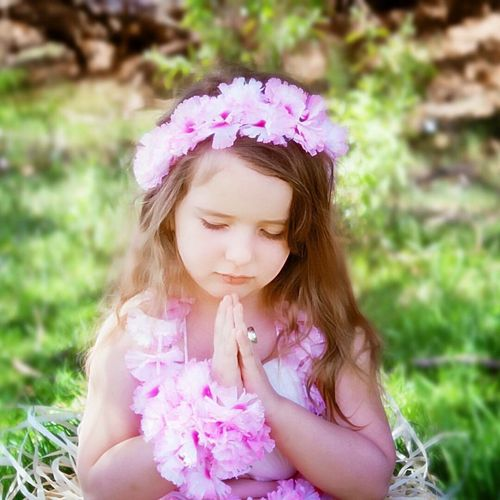 Cute girl praying while wearing floral crown on field