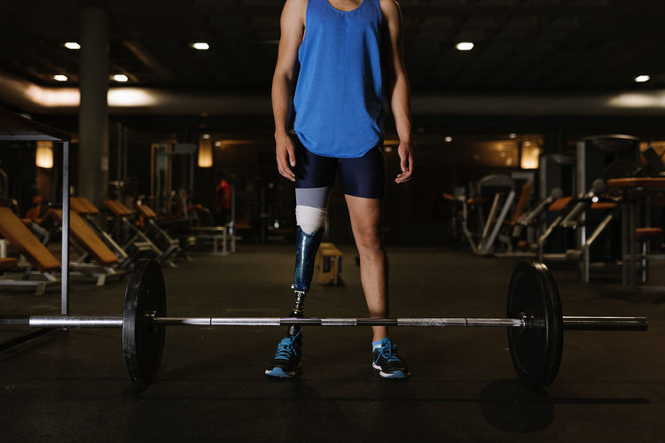 Full length of man with prosthetic legs exercising in gym