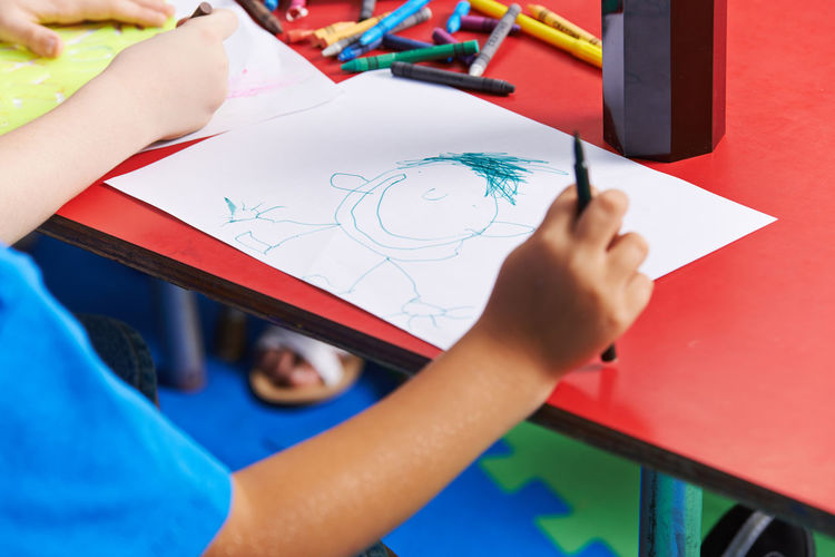 Midsection of boy drawing in classroom