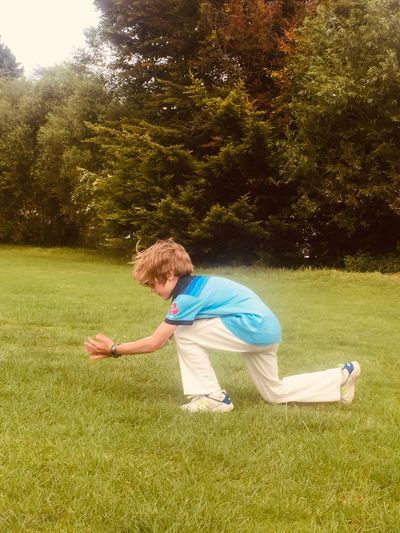 Side view of boy playing on field