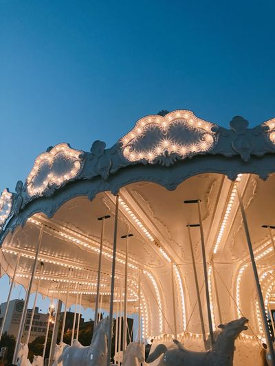 Low angle view of illuminated carousel against clear blue sky