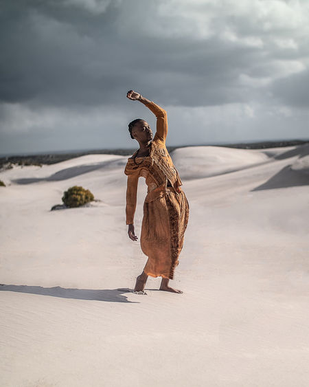 Full length of young man wearing traditional clothing standing at desert