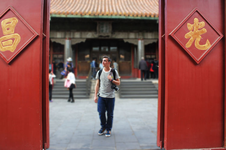 Forbidden City Through The Door Adult Architecture Communication Connection Day Door Doorway Emotion Full Length Holding Lifestyles Mobile Phone One Person Outdoors Real People Red Smiling Technology Telephone Using Phone Walking Wireless Technology Young Adult The Modern Professional A New Perspective On Life 2018 In One Photograph Redefining Menswear The Traveler - 2019 EyeEm Awards