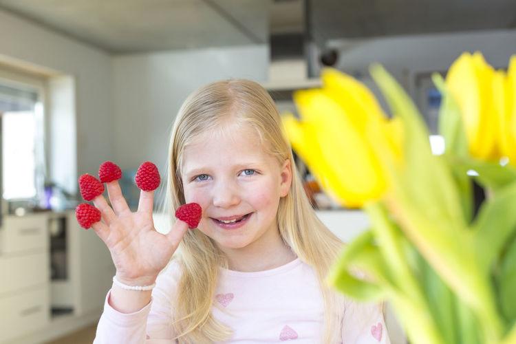 Portrait of smiling girl holding raspberries at home