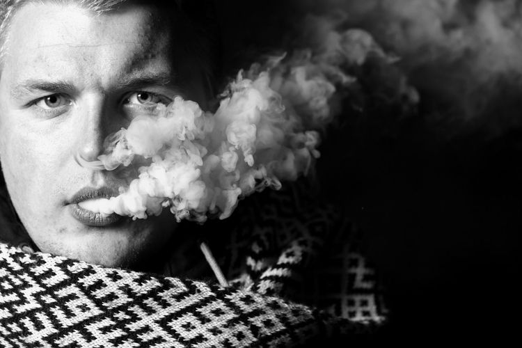 Close-up portrait of young man smoking outdoors