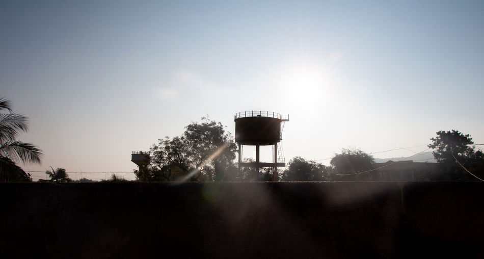 Silhouette of water tower against sky