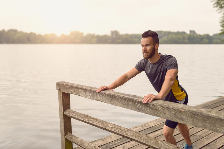 Young man doing stretching exercises on a deck Ac Beard Bearded Day De Deck Exercise Fit Fitness Healthy Male Man Muscles One Person Outdoors Park Sport Stretching Wooden Young Young Adult