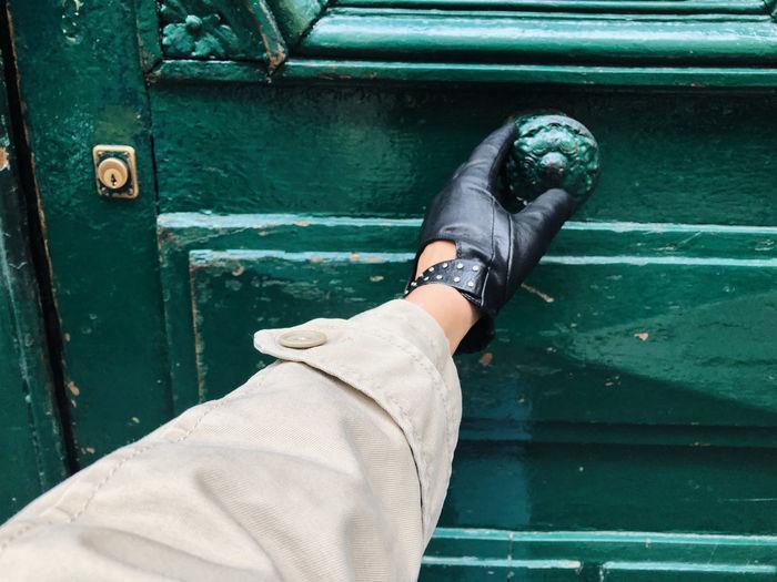 Hand opening a green door